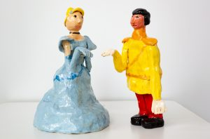 Two ceramic sculptures. A blonde woman in a fancy blue dress with blue gloves on the left with her hand out in front of her. And a black-haired man with red pants, yellow jacket and black shoes with his hand towards the woman.