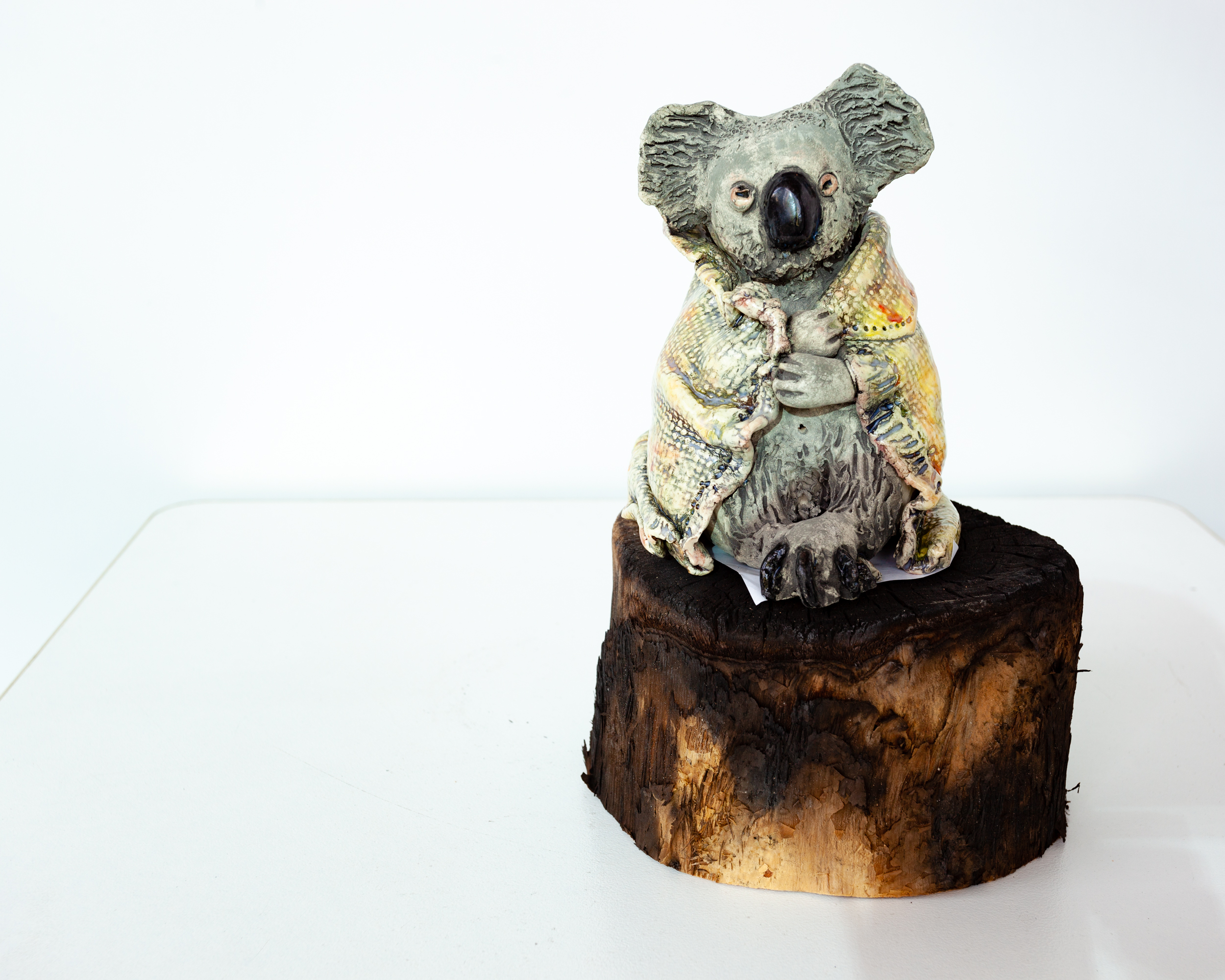 A ceramic koala with a blanket sitting on a charred piece of round wood